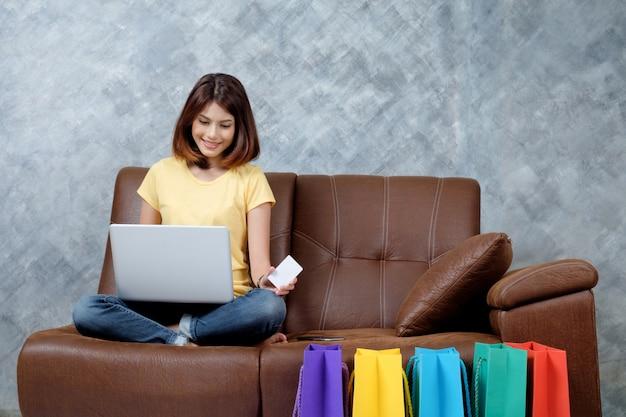 Mulher fazendo compras online. segurando cartão de crédito em branco.