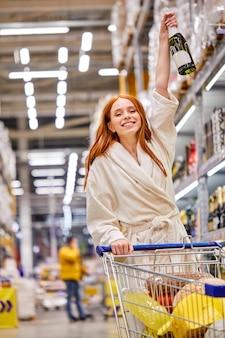 Mulher fazendo compras sozinha, comprando álcool, segurando champanhe nas mãos, sorrindo feliz, em roupão de banho. mulher vai comemorar feriados
