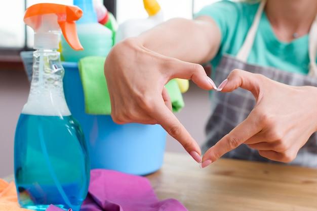 Mulher fazendo coração com os dedos na frente de produtos de limpeza