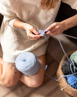 Mulher fazendo crochê em ângulo alto