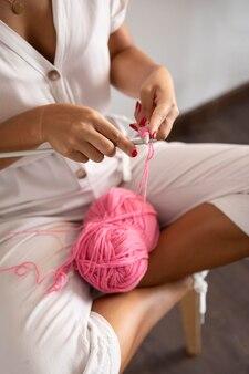 Mulher fazendo crochê em casa