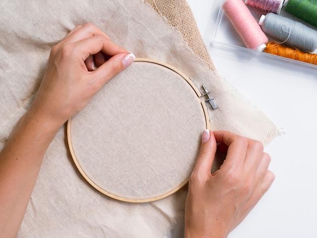 Mulher fazendo decorações com anéis de madeira e tecido