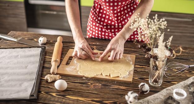 Mulher fazendo deliciosos biscoitos caseiros em forma de coração na cozinha