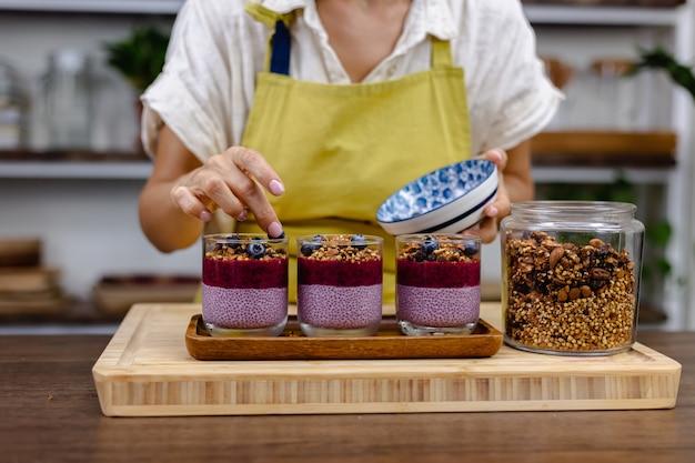 Mulher fazendo deliciosos pudins de chia do deserto com morango e mirtilo, leite de amêndoa com fruta do dragão em pó rosa e granola na cozinha em casa.