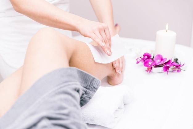 Mulher fazendo depilação nas pernas em um salão de beleza