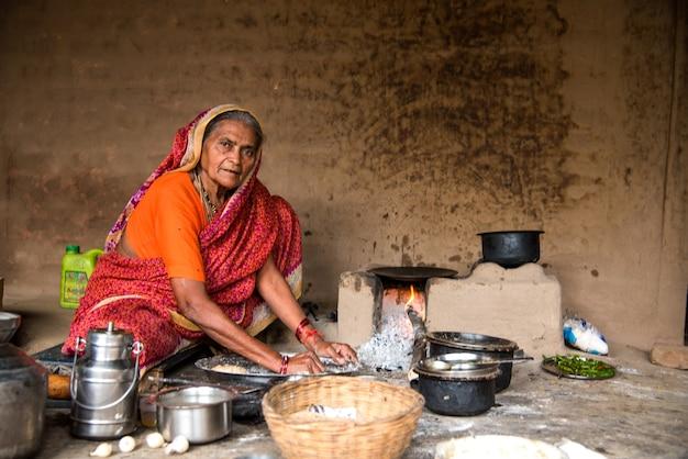 Mulher fazendo e cozinhando alimentos frescos em uma vila rural em uma cozinha vintage
