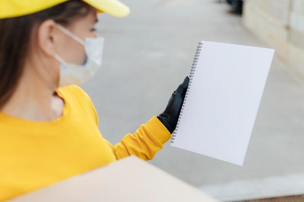 Mulher fazendo entrega de close-up usando máscara