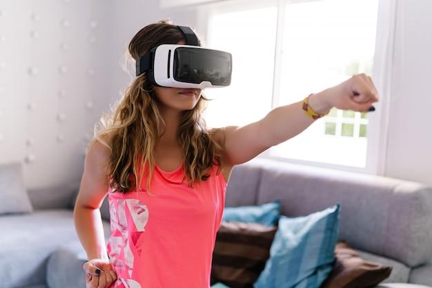 Mulher fazendo esporte com óculos de realidade virtual em casa
