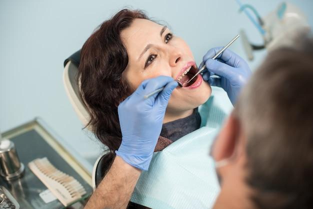Mulher fazendo exame odontológico em consultório odontológico