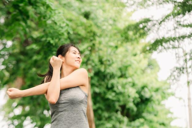 Mulher fazendo exercício de alongamento do ombro antes de correr