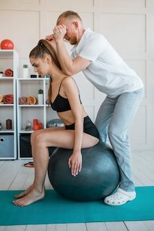 Mulher fazendo exercícios com bola e fisioterapeuta