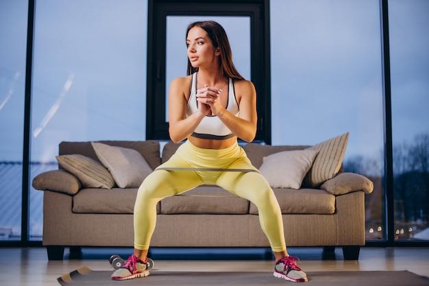 Mulher fazendo exercícios com elástico em casa