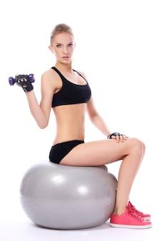 Mulher fazendo exercícios com halteres na bola de fitness