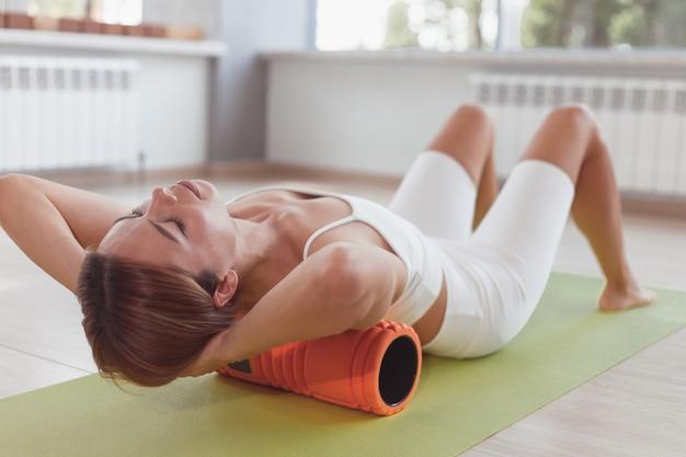 Mulher fazendo exercícios com rolo de espuma para aliviar a dor nas costas