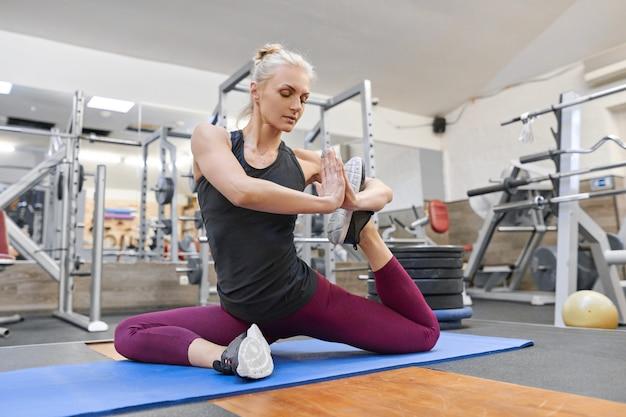 Mulher fazendo exercícios de alongamento no ginásio, mulher praticando ioga