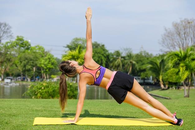 Mulher fazendo exercícios de alongamento no tapete de fitness