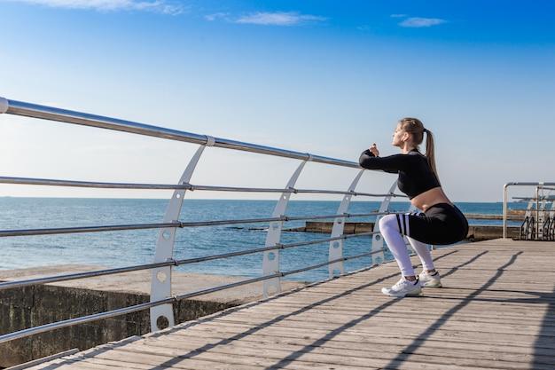 Mulher fazendo exercícios de aquecimento e agachamentos.