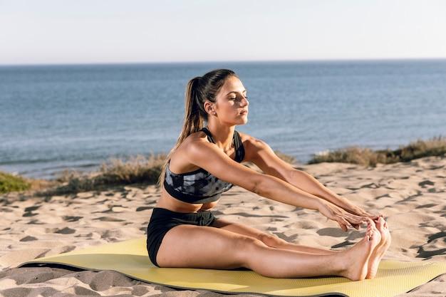 Mulher fazendo exercícios de aquecimento no tapete de fitness