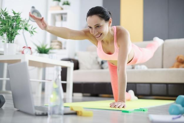 Mulher fazendo exercícios de equilíbrio em casa. exercício online para o conceito de perda de peso em casa
