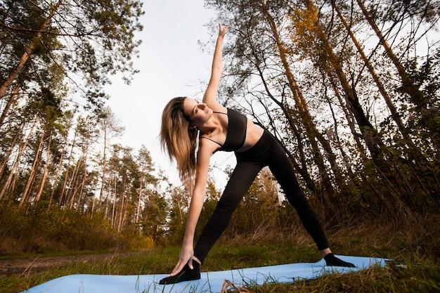 Mulher fazendo exercícios de ioga ou pilates. em pé na pose de ioga do triângulo. conceito de estilo de vida saudável. treino ao ar livre. jovem de sutiã preto e leggins relaxantes em yoga asana, praticando posições.
