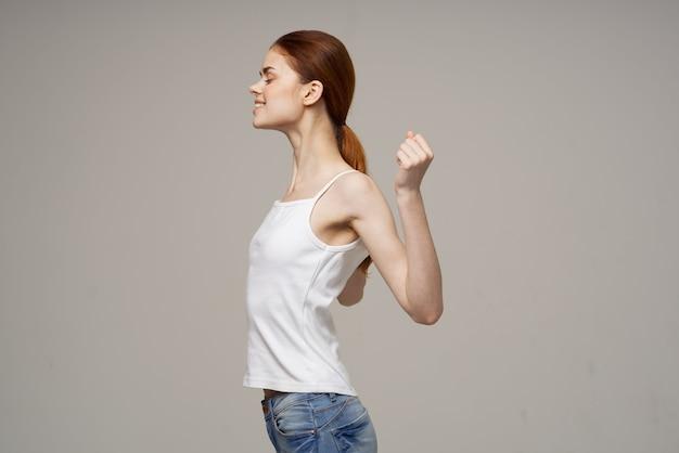 Mulher fazendo exercícios de ombro saúde fundo cinza