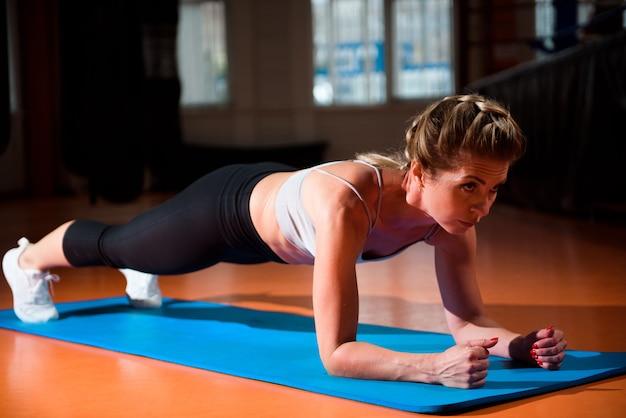 Mulher fazendo exercícios de prancha no ginásio.