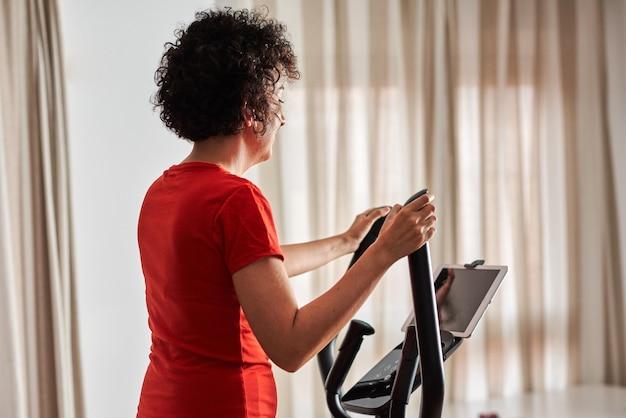 Mulher fazendo exercícios em casa com aula elíptica de cross training online