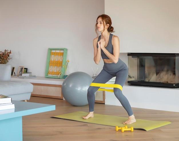 Mulher fazendo exercícios em casa com banda