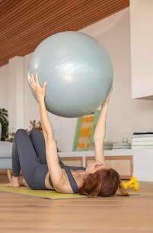 Mulher fazendo exercícios em casa no tatame