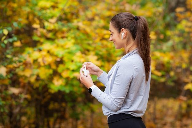 Mulher fazendo exercícios no parque e ouvindo música