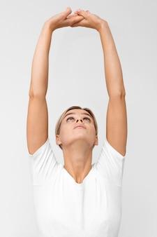 Mulher fazendo fisioterapia enquanto levanta os braços