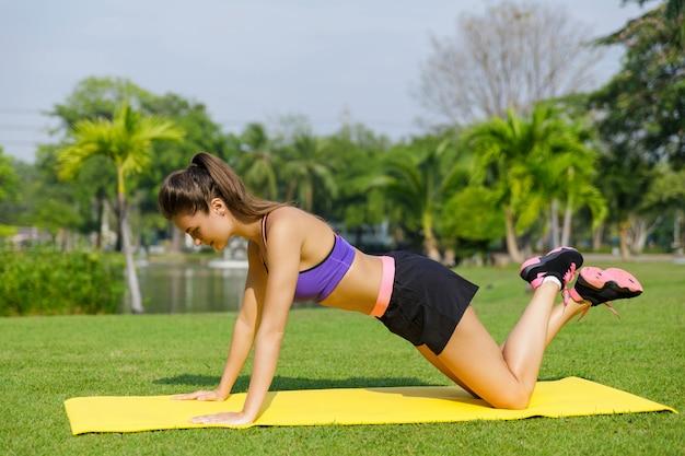 Mulher fazendo flexões de joelho exercita-se no parque