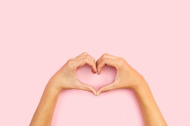 Mulher fazendo formato de coração com as duas mãos em um fundo rosa