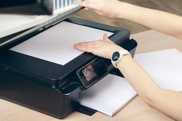 Mulher fazendo fotocópia usando copiadora no escritório