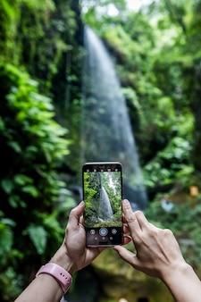 Mulher fazendo fotografia móvel em cascada de los tilos em isla de la palma, ilhas canárias