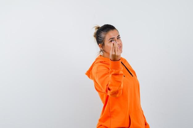 Mulher fazendo gesto italiano com um capuz laranja e parecendo confiante