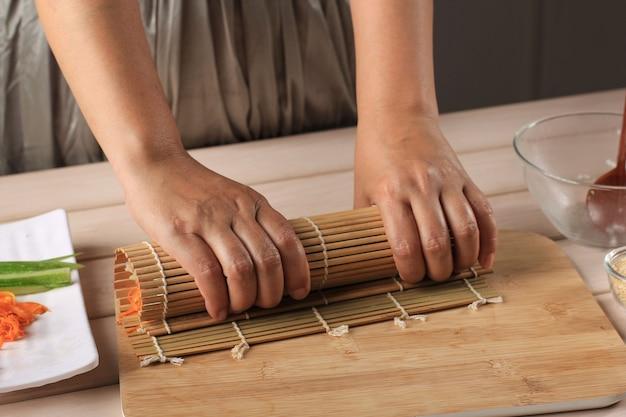 Mulher fazendo gimbap rolo coreano gimbap (kimbob ou kimbap) feito de arroz branco cozido no vapor e vários outros ingredientes, como kyuri, cenoura, salsicha, pau de caranguejo ou kimchi. envolvido com lavador de algas marinhas.