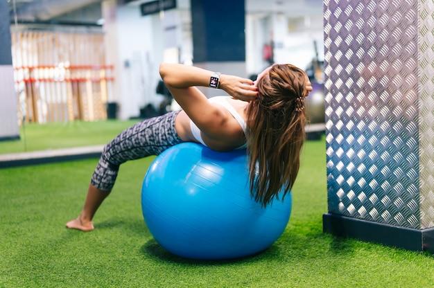 Mulher fazendo ginástica em uma bola de plástico