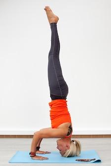 Mulher fazendo headstand no tapete
