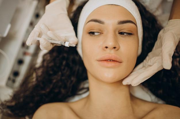 Mulher fazendo injeções em cosmetologista