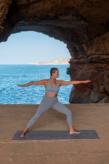 Mulher fazendo ioga à beira-mar, foto completa