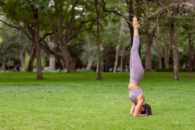 Mulher fazendo ioga asanas no parque, na grama com árvores ao fundo