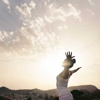 Mulher fazendo ioga e alonga seu corpo
