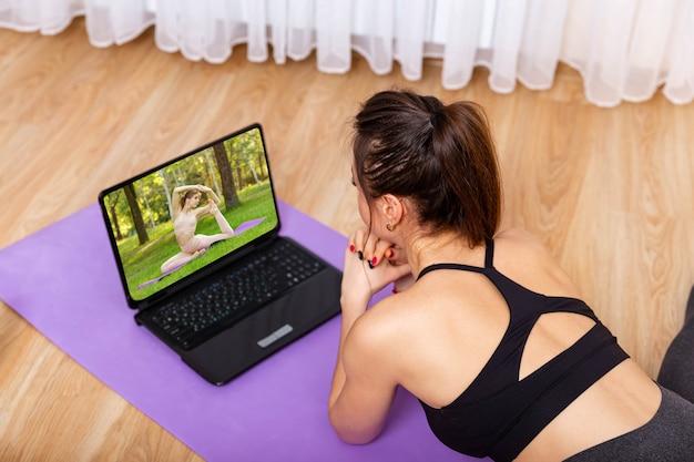 Mulher fazendo ioga e assistindo a aulas online em casa