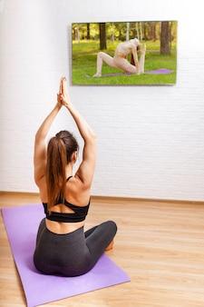 Mulher fazendo ioga e assistindo aulas online em casa na tv
