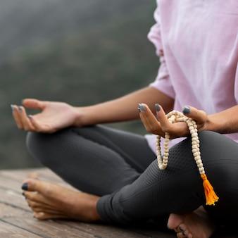 Mulher fazendo ioga e segurando um rosário