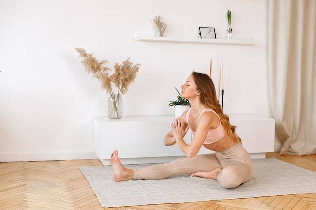 Mulher fazendo ioga em casa em uma bela sala de estar