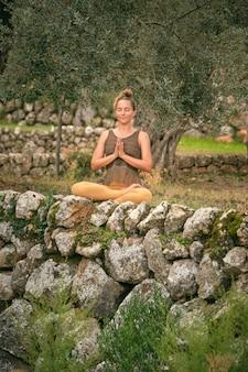 Mulher fazendo ioga em padmasana com as mãos namastê