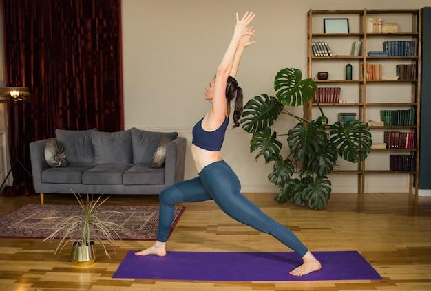 Mulher fazendo ioga fazendo pose de virabhadrasana em um tapete em uma sala