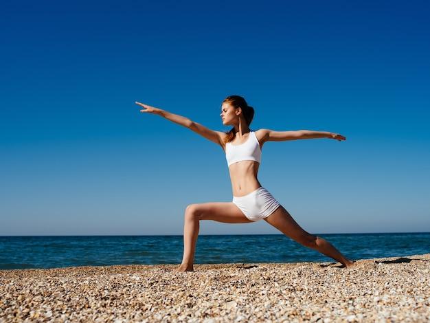 Mulher fazendo ioga na praia oceano verão